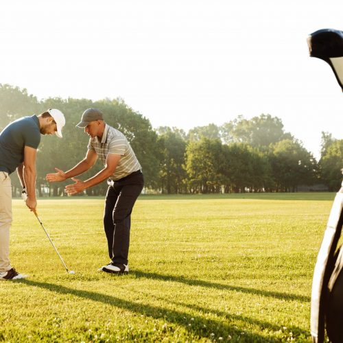 Young sportsman practicing golf with his teacher while standing on a green course